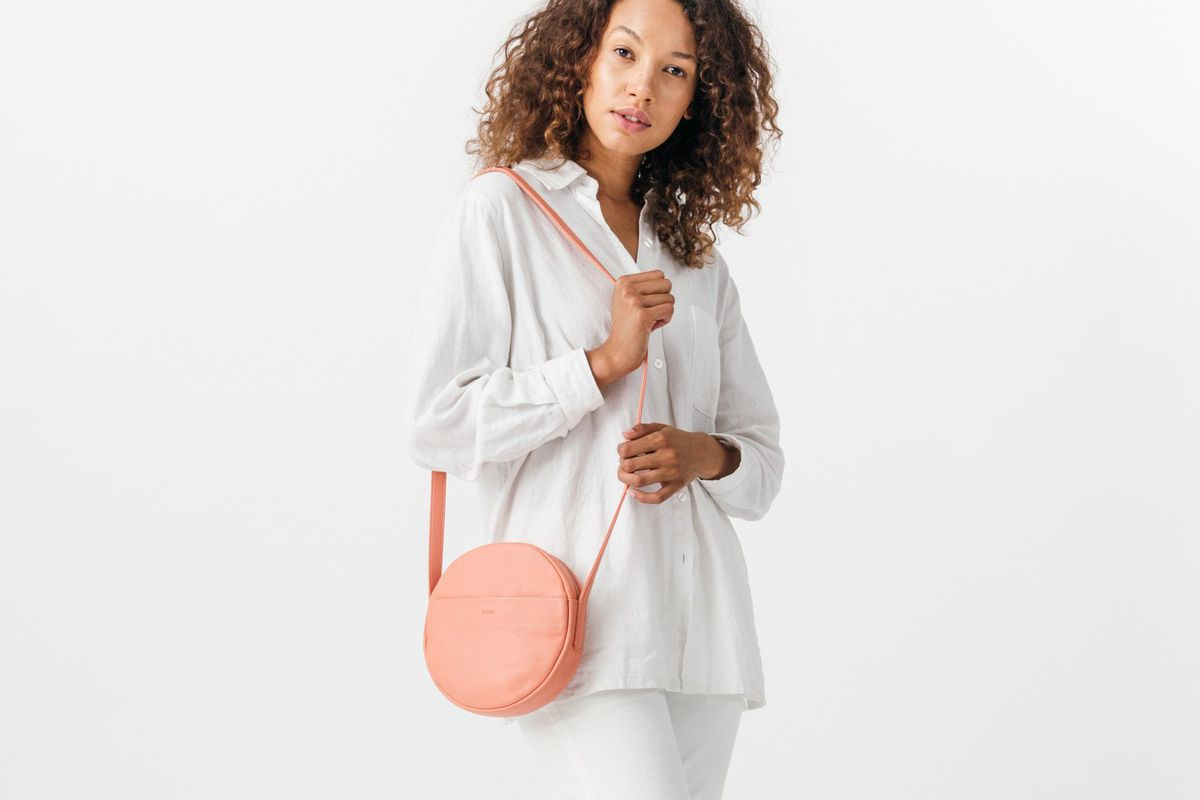 A woman with a pink crossbody purse in the shape of a circle.