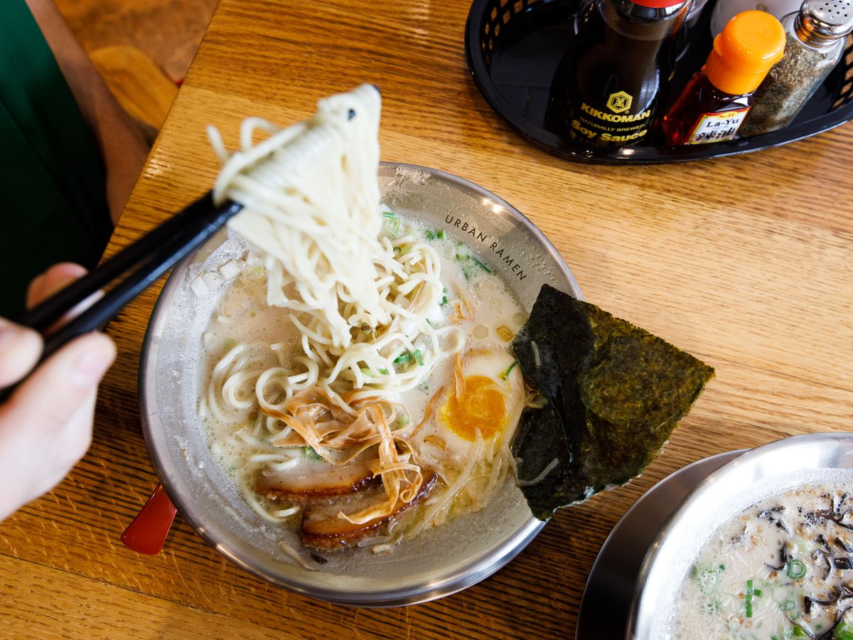 A hand holding a pair of black chopsticks lifts noodles from a cloudy bowl of ramen.