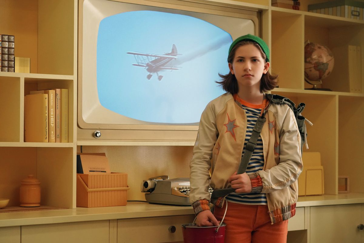 a girl in mismatched clothes standing in front of an old-fashioned tv