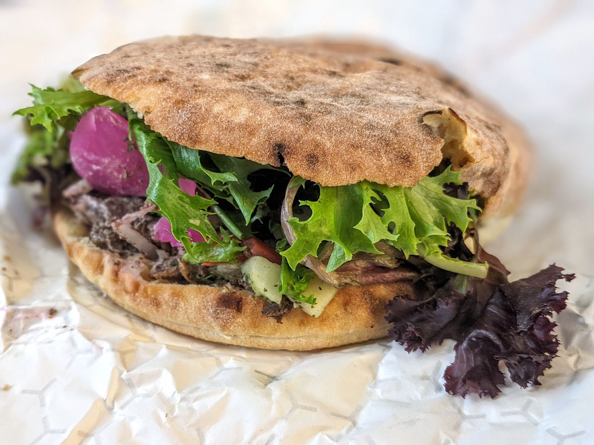 Closeup on a pita stuffed with greens, red onions, and shredded meat. It's sitting on a slightly crumpled white paper.
