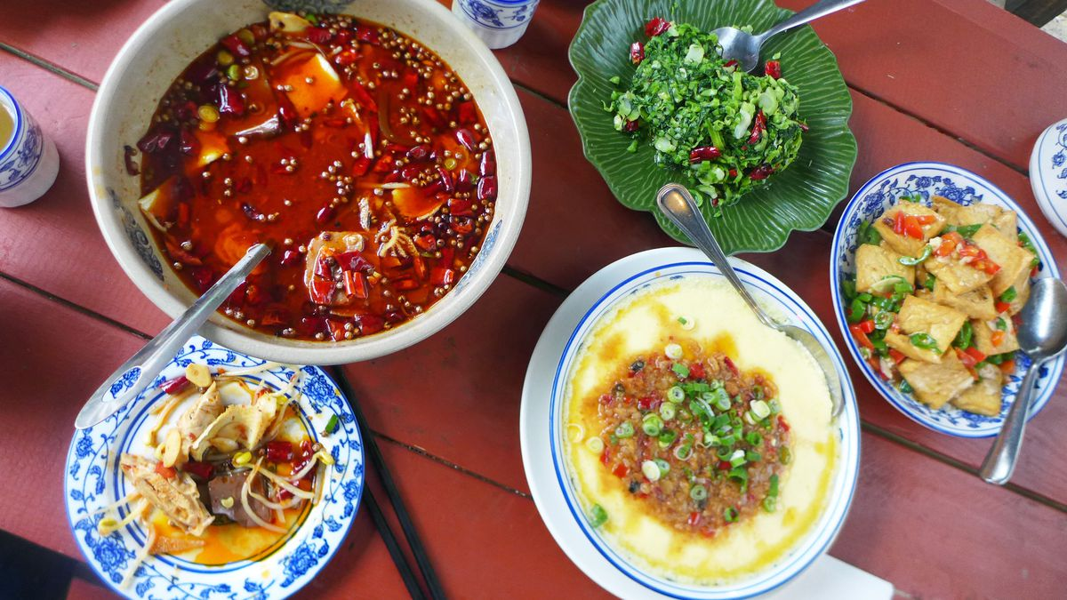In bowls and blue china, five dishes from the restaurant on a red picnic table.