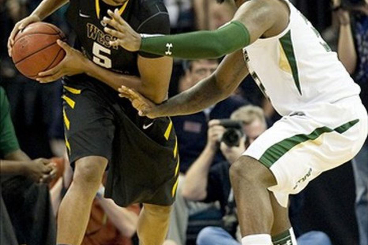 March 3, 2012; Tampa, FL, USA; West Virginia Mountaineers forward Kevin Jones (5) looks to pass while guarded by South Florida Bulls forward Toarlyn Fitzpatrick (32) at the Tampa Bay Times Forum.  Mandatory Credit: Jeff Griffith-US PRESSWIRE