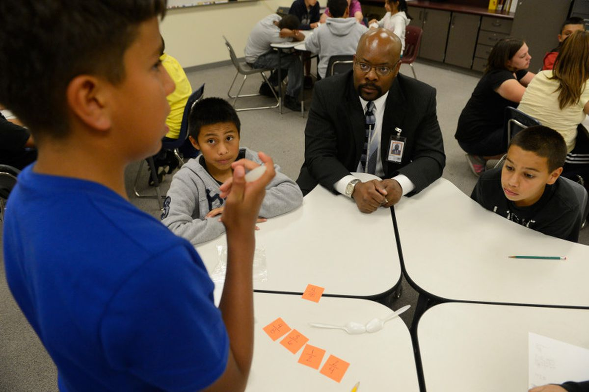 A boy in a blue shirt works on a math card game problem with two other students seen at the table while Superintendent Rico Munn sits on the corner of the table, wearing a black suit and tie.