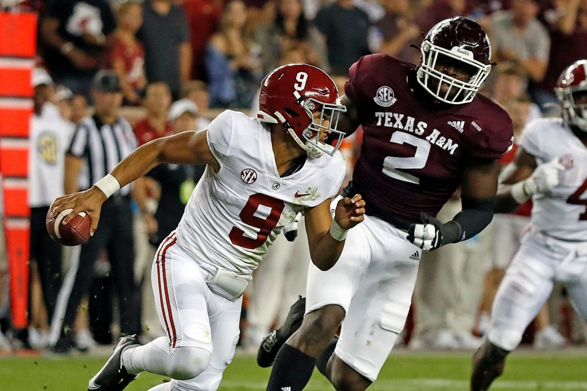 Bryce Young of the Alabama Crimson Tide is forced out of the Micheal Clemons of the Texas A&M Aggies at Kyle Field on October 09, 2021 in College Station, Texas.