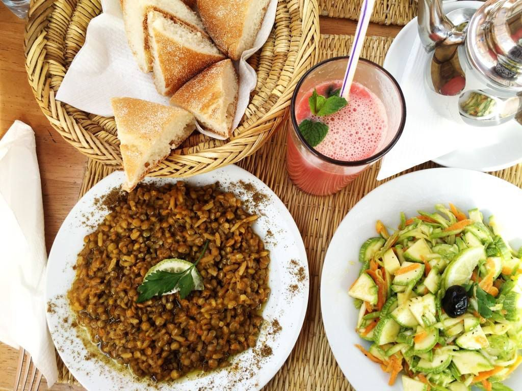 From above, a thatch wooden table with a plate of grains, a vegetable plate, and a basket of triangular flatbreads, beside a tall glass of fruit juice garnished with mint