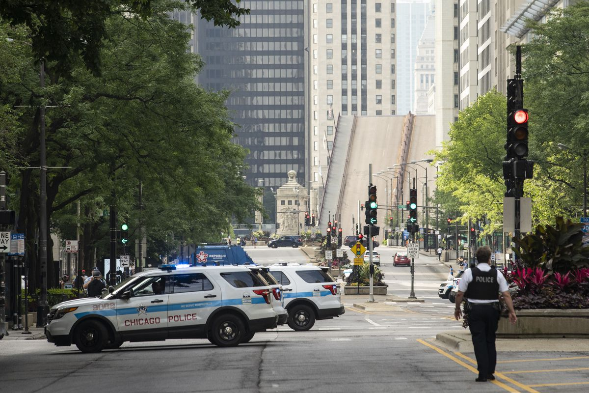 Chicago Police stand guard on the Magnificent Mile and the Michigan Avenue Bridge over the Chicago River is lifted after looting broke out overnight in the Loop and surrounding neighborhoods, Monday morning, Aug. 10, 2020.