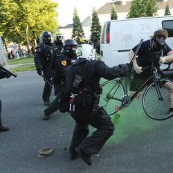 Police confront a protester decrying the police shooting of Bernardo Palacios-Carbajal in Salt Lake City on Thursday, July 9, 2020.