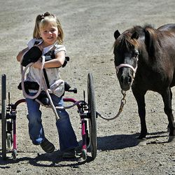 Brianna Heim, 5, walks Bella at Buffalo Ranch in Farmington on Thursday as part of a therapeutic riding program organized by the nonprofit group Therapeutic Assets.