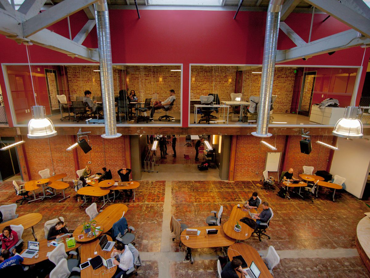 The interior of a co-working space called Impact Hub Oakland in California. There are multiple tables, chairs, and offices. The ceilings are high and there are hardwood floors.