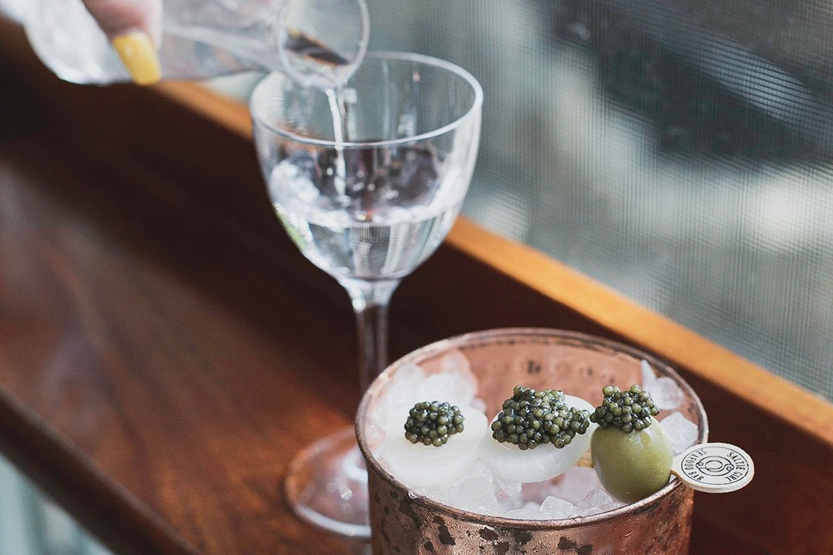 A hand pours a vodka martini from a carafe to a glass, and garnishes, including caviar, chill over ice nearby