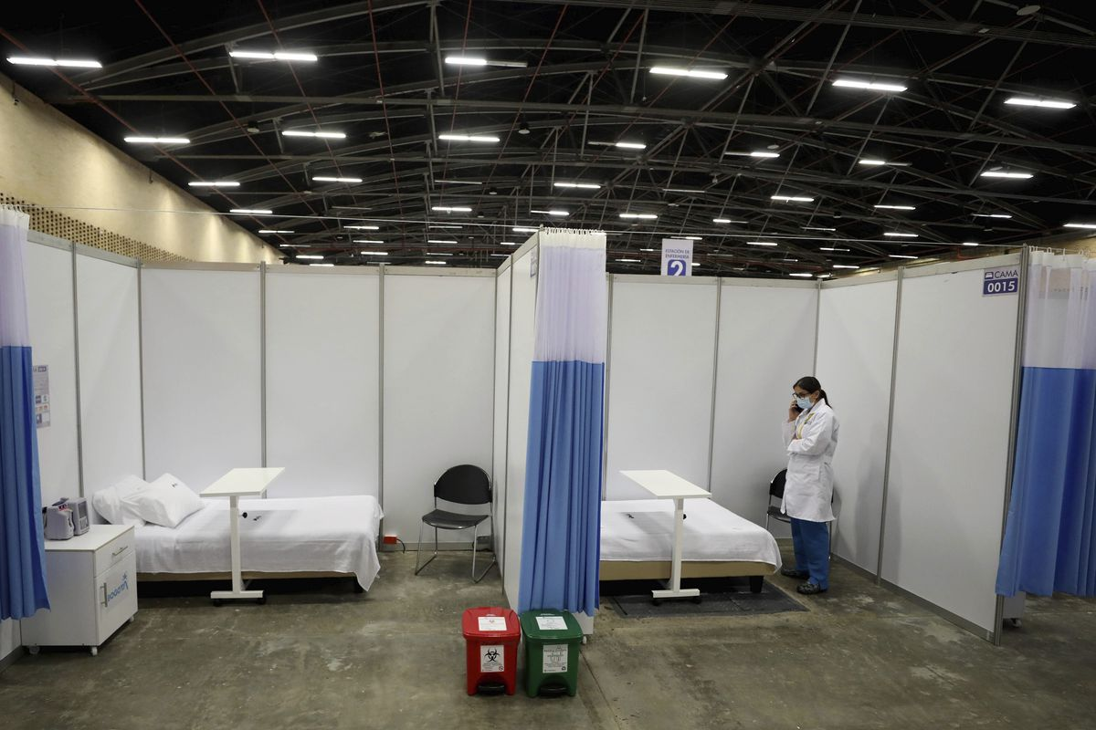 A doctor talks on her cell at a field hospital set up inside the Corferias convention center in Bogota, Colombia, Monday, April 20, 2020. Corferias is a space that normally hosts fairs and conferences that was rehabilitated as a field hospital for non-COVID19 patients, to create more space for COVID-19 patients at proper hospitals. (AP Photo/Fernando Vergara)
