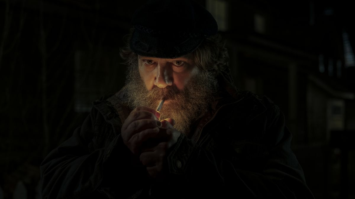 A heavily bearded man lights a cigarette in the dark, lighting up his face dramatically, in Midnight Mass