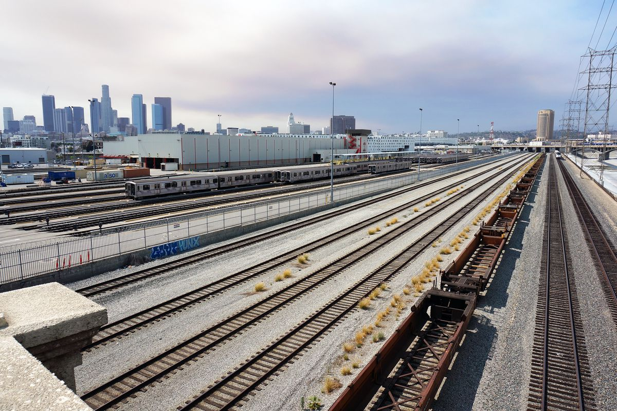 Trains sit on tracks with Downtown in background