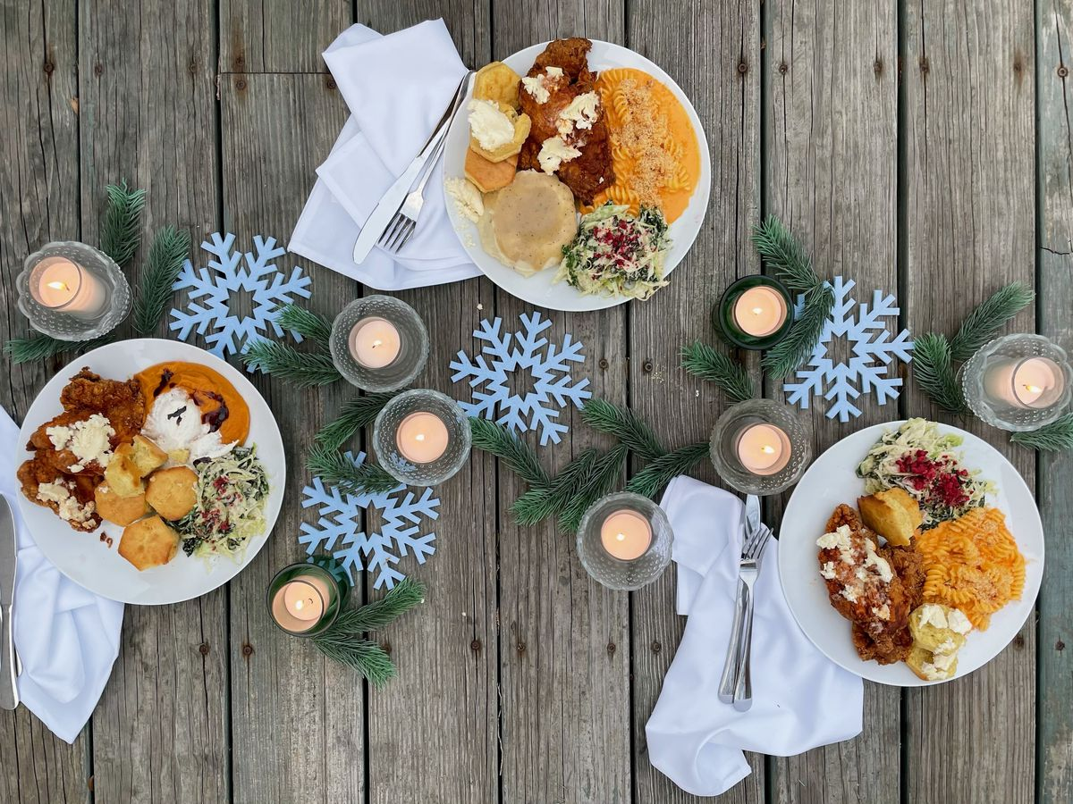 Three plates of fried chicken and sides laid out on a table alongside candles and winter decorations.