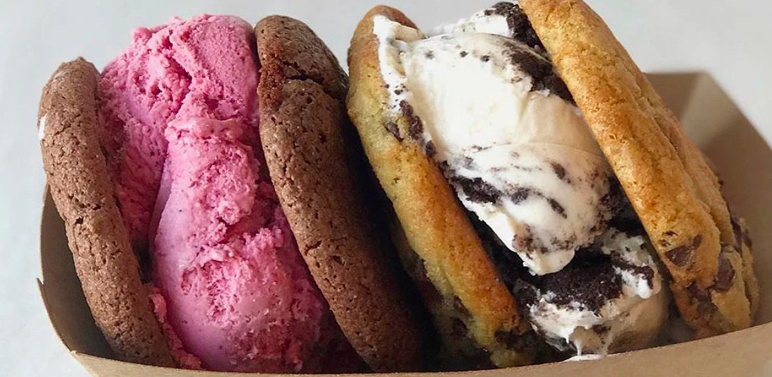 Two cookie ice cream sandwiches sit side by side in a white paper container. One has a pinkish red ice cream in it, while the other has a white ice cream with crumbled Oreos in it.