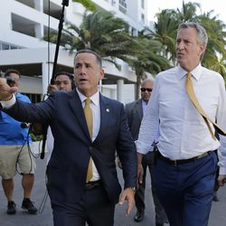 Miami Beach Mayor Philip Levine, left, talks to New York City Mayor Bill de Blasio, right, as they tour where the city has raised streets and installed pumps to combat rising tides, Thursday, June 23, 2017, in Miami Beach, Fla. The U.S. Conference of Mayors opens its annual meeting Friday in Miami Beach. Mayors of cities with populations of 30,000 or more will discuss plans to reduce the nation's carbon footprint and protect immigrant families.
