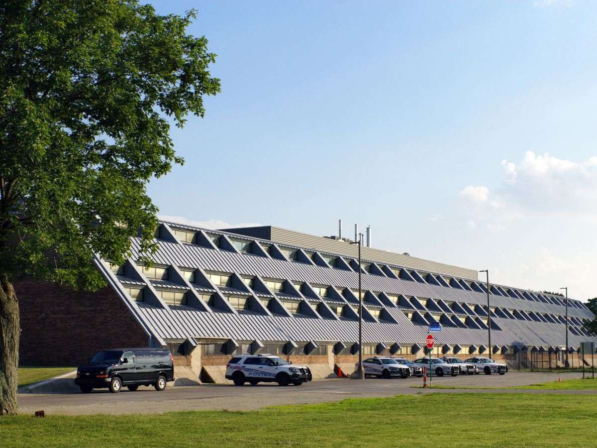 A long building with a slanted metal roof and skylights that stretches nearly to the ground. A few police cars sit in the parking lot.