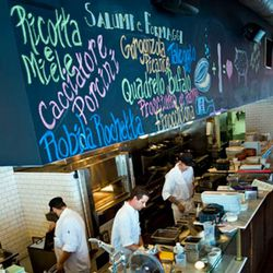 Colorful chalkboard above open kitchen with daily salumi and formaggi listed.