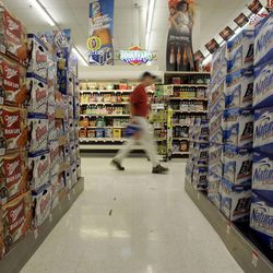 A man carries a case of beer as products from Coors, Miller and Anheuser-Busch are stacked in a grocery store Tuesday, Oct. 23, 2007, in St. Louis. Few things have the power to derail young lives as thoroughly as alcohol or drugs, but parents are often oblivious to the signs — and to the messages they have sent their children that may encourage it. Prevention has to start early.