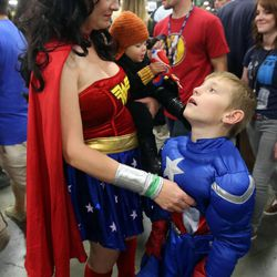 Laurisa Dixon, dressed as Wonder Woman, holds her daughter Cassandra, dressed as Black Widow from The Avengers, while talking to her son Charlie, as Captain America, at Comic Con at the Salt Palace Convention Center in Salt Lake City on Saturday, Sept. 7, 2013.