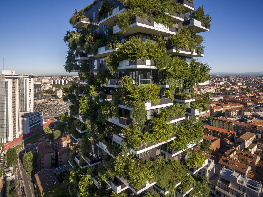 The exterior of the Bosco Verticale in Milan. The tall apartment building has balconies with many trees and plants.