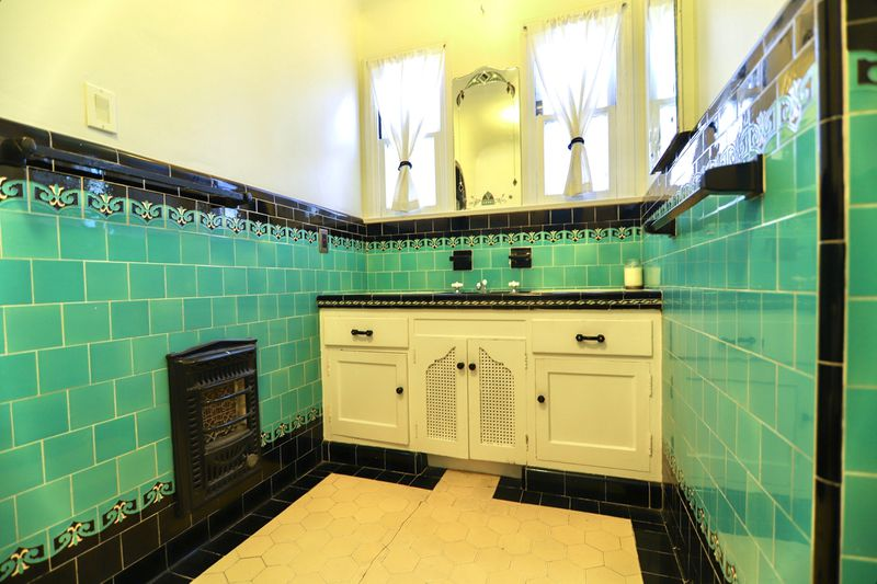 Bathroom with teal tiles and white cabinets.