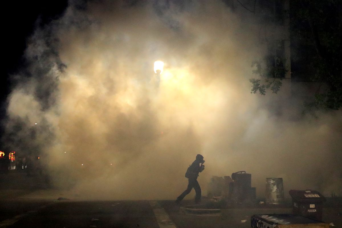 A demonstrator runs through tear gas that was deployed by police officers during a protest sparked by the death of George Floyd while in police custody on May 29, 2020 in Oakland, California.