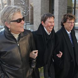 Plaintiff's Laurie Wood, left, and her partner, Kody Partridge, center, walk with their attorney Peggy Tomsic, after leaving the Frank E. Moss United States Courthouse on Wednesday, Dec. 4, 2013, in Salt Lake City. A challenge to Utah's same-sex marriage ban by three gay couples is back in court Wednesday as a federal court judge heard arguments in a case.
