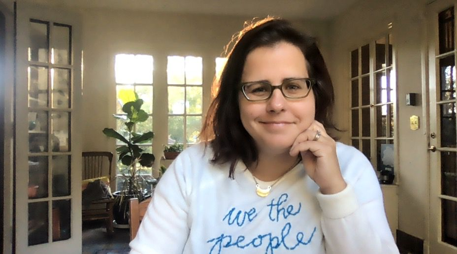 """Kat McRitchie smiling at the camera wearing a shirt that reads """"we the people"""" in blue cursive."""