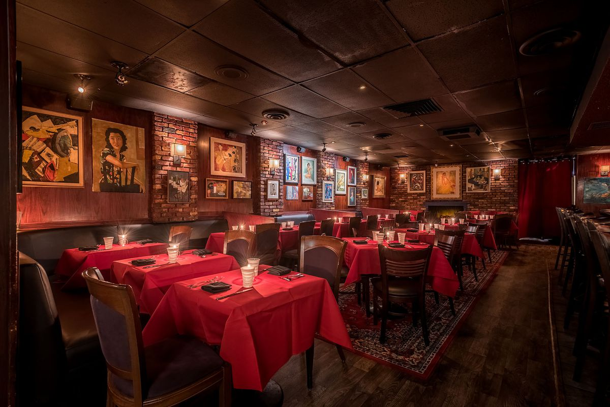 A dimly-lit, red-tinged old school steakhouse dining room, ringed with paintings.