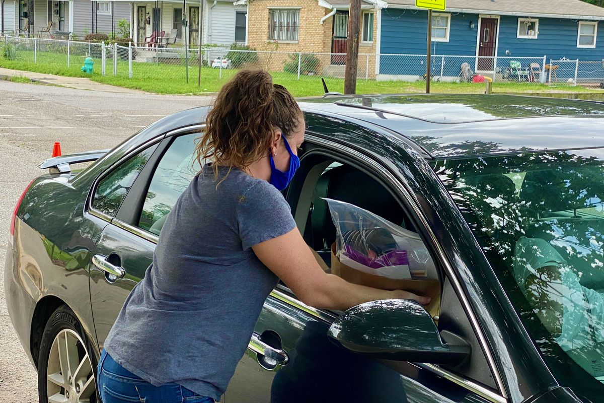 Woman hands a bag of remote learning supplies in to a car.