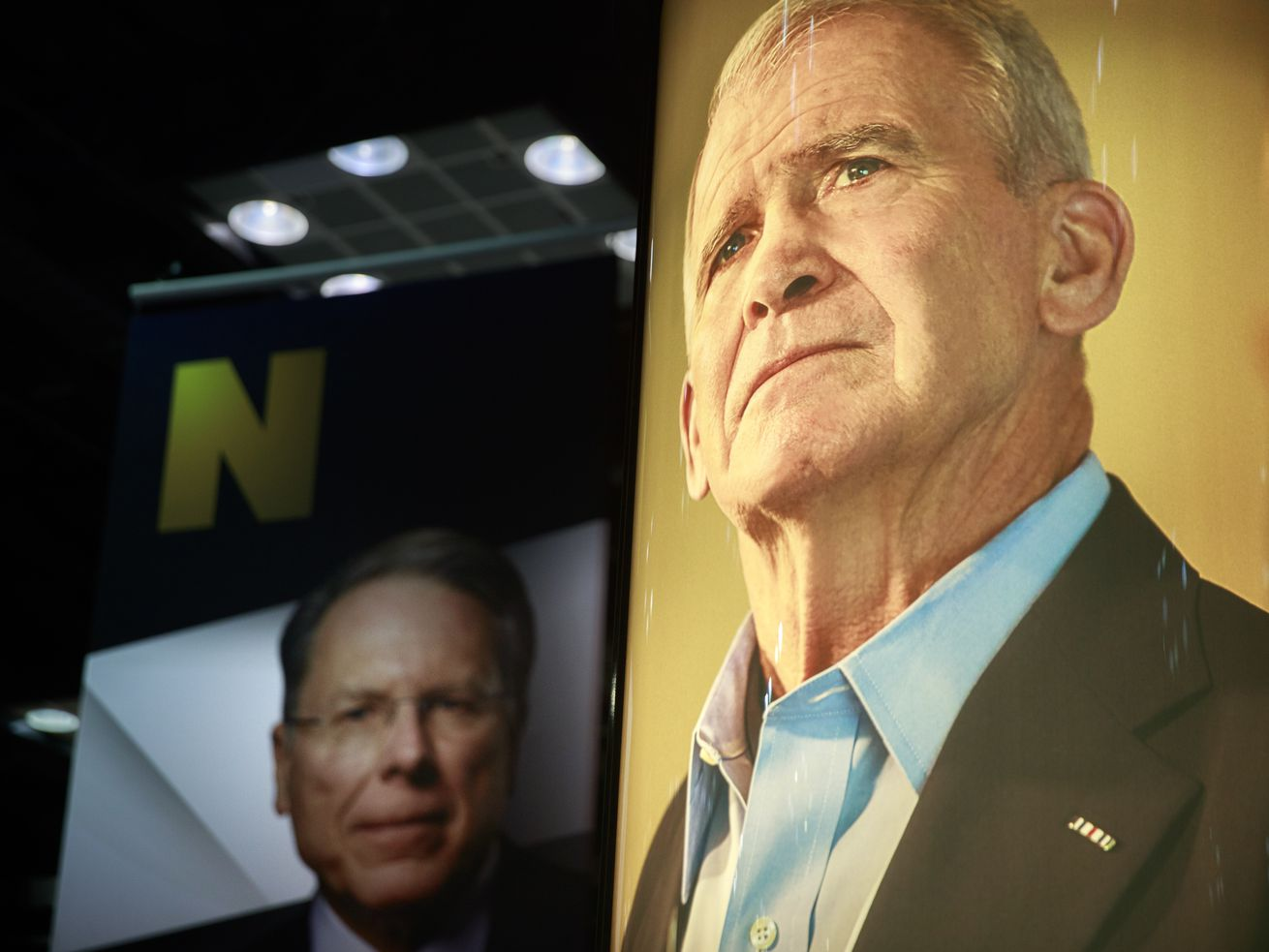 Photos of NRA Chief Executive and Executive Vice President Wayne LaPierre (L) and former president of the NRA Oliver North (R) are on display during the third day of the National Rifle Association convention being held nearby.