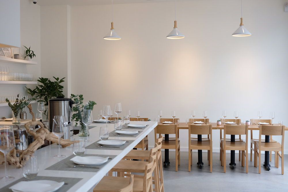 A white dining room with blonde wood chairs