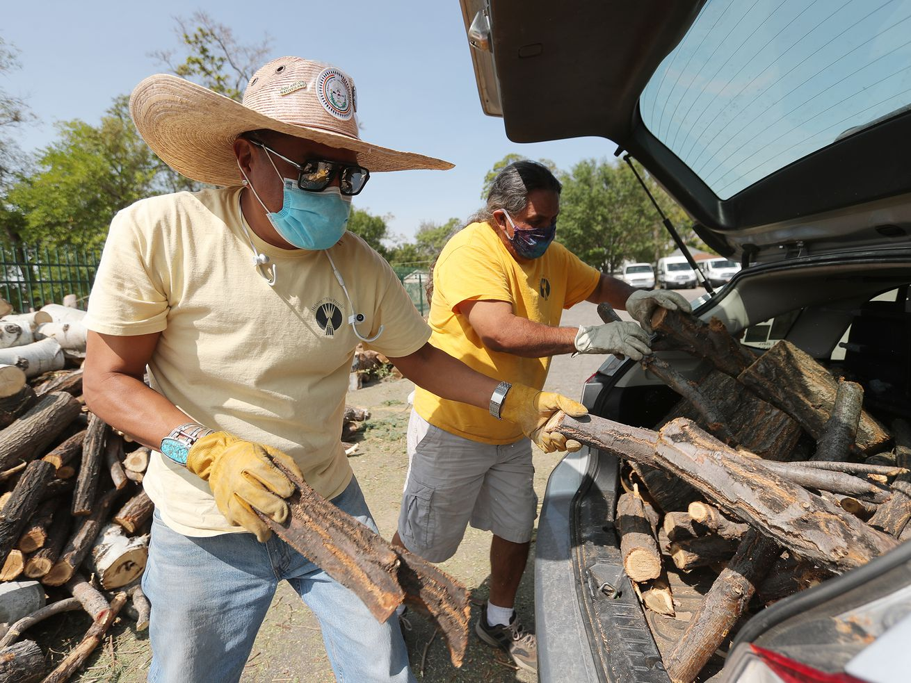 Gabe Brodie and Nino Reyos unload wood from a car at the The Urban Indian Center of Salt Lake on Sunday, Sept. 13, 2020. The wood will be taken to the Navajo Nation to be given to their elders.