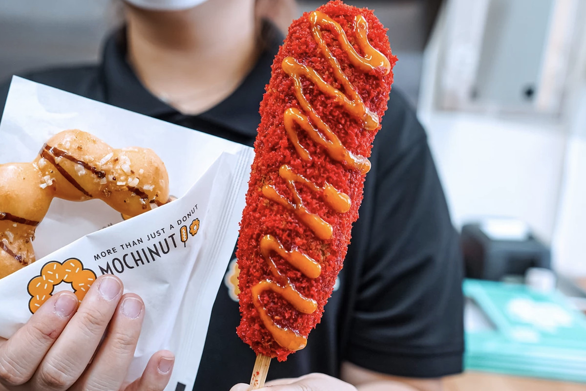A person holds a mochi doughnut and a corn dog on a stick covered in bright red powder