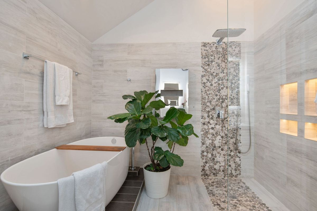 A bathroom with a large soaking tub, a tall potted fiddle leaf fig, and a walk-in glass rain shower.