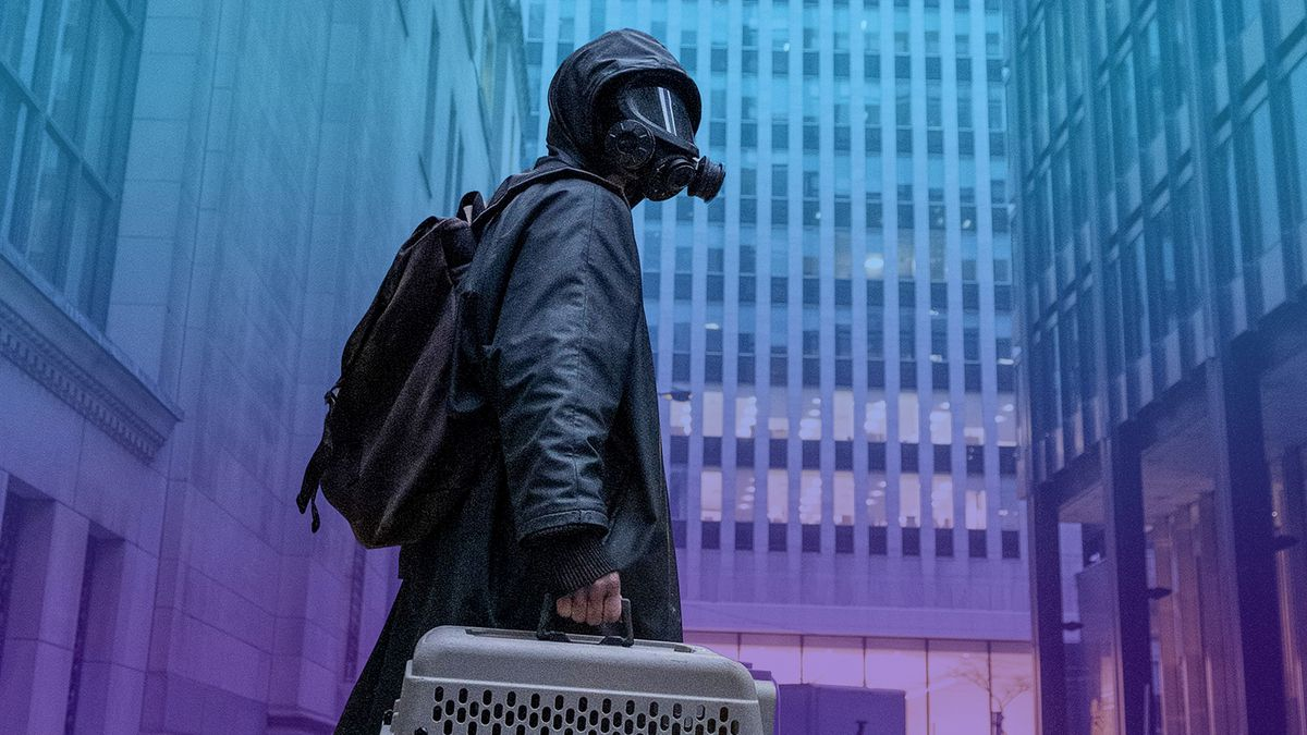 Photo of Yorick Brown (Ben Schnetzer) wearing a waterproof coat and wearing a gas mask stands atop a car carrying an animal crate