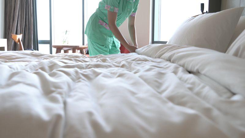 Housekeeper making a hotel bed.