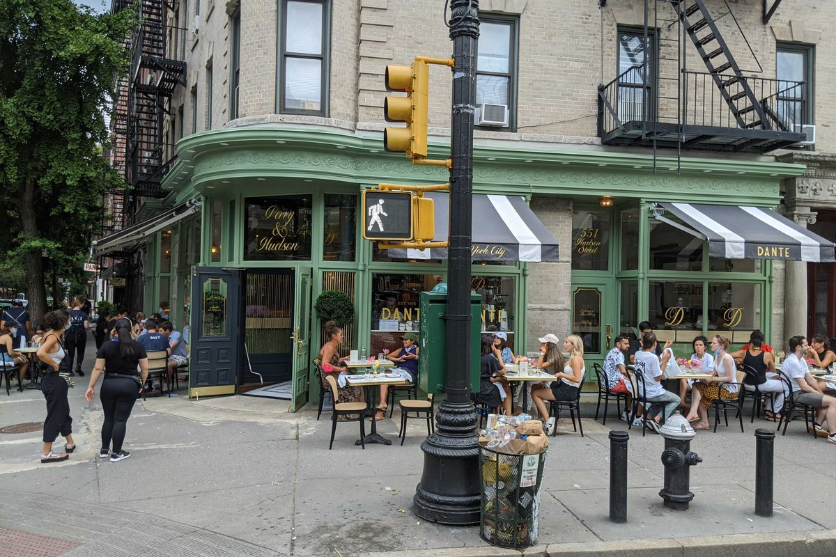 The exterior of a restaurant with a traffic light pole in the center of the image. Further in, people are seated at tables and chairs