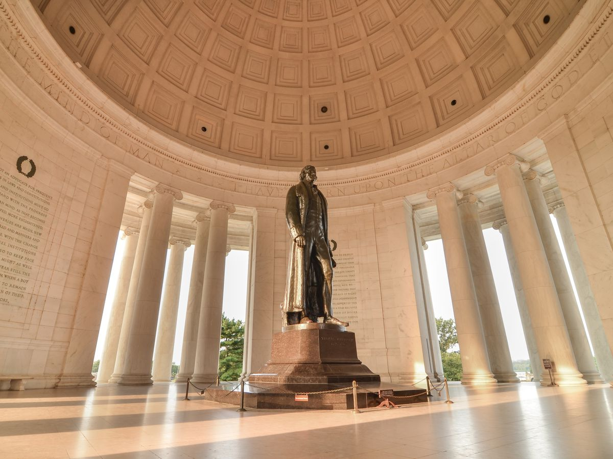 The interior of the Jefferson Memorial in Washington D.C. The roof is domed and there is a statue of a man in the center of the room.