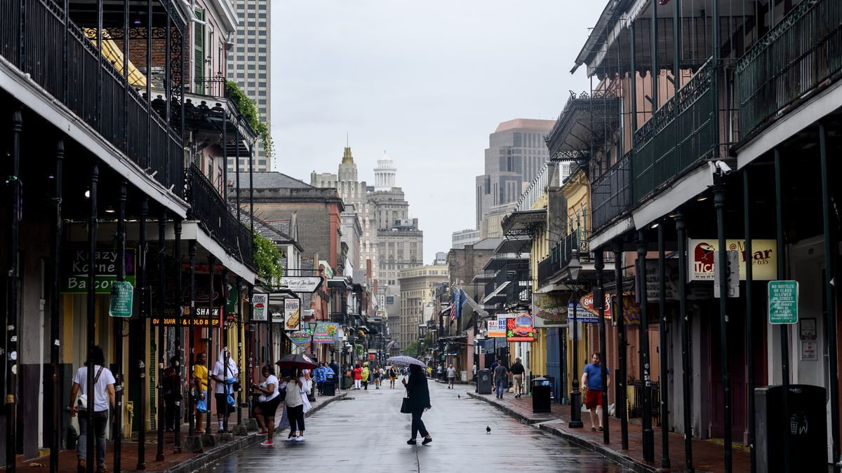 A woman holding an umbrella walks down a rainy Bourbon Street in the city of New Orleans.