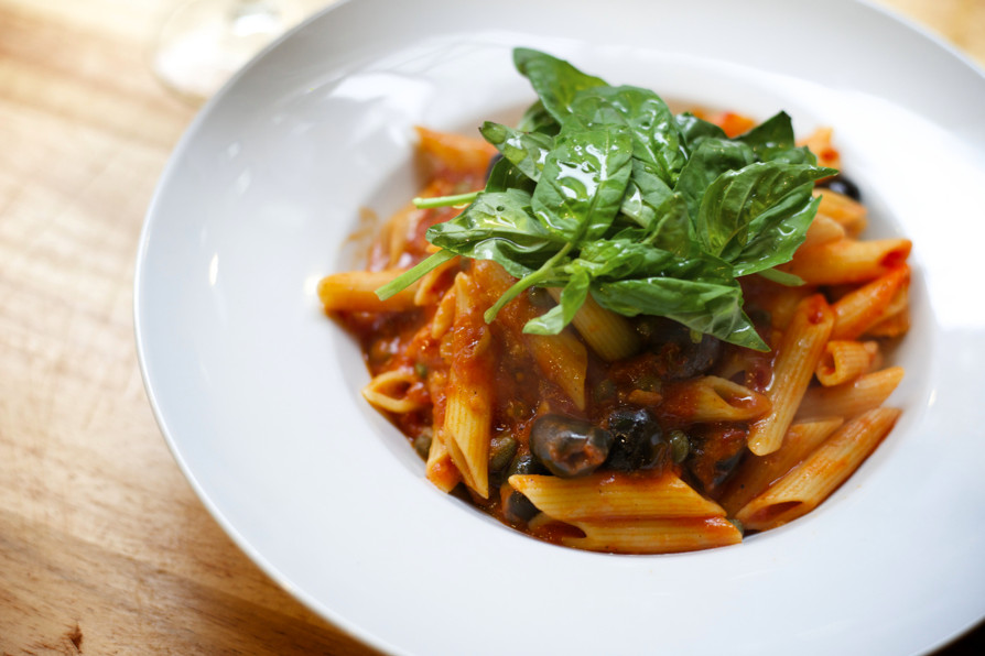 Ziti in tomato sauce, topped with basil, on a white plate
