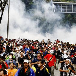 Protesters run as riot police fire tear gas at demonstrators during an anti-Internal Security Act (ISA) protest near the National Mosque in Kuala Lumpur, Malaysia, Saturday.