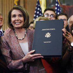 House Speaker Nancy Pelosi of Calif., holds up a copy of the revised Health Care and Education Reconciliation Act, during a bill enrollment ceremony on Capitol in Washington, Friday.