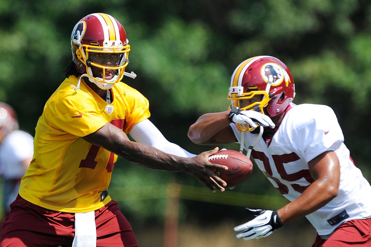 ASHBURN, VA - JULY 26:  Robert Griffin III #10 hands the ball off to Evan Royster #35 of the Washington Redskins during training camp at Redskins Park on July 26, 2012 in Ashburn, Virginia.  (Photo by Patrick McDermott/Getty Images)