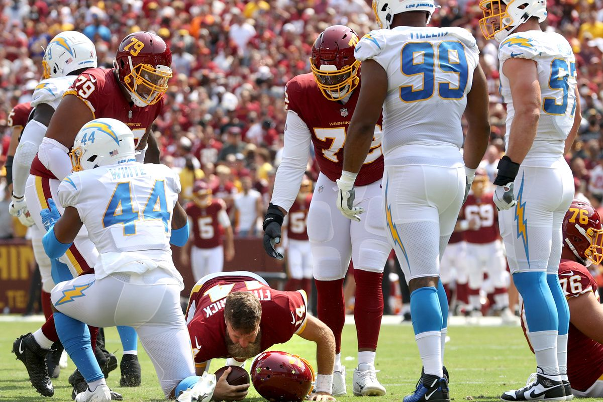 Ryan Fitzpatrick #14 of the Washington Football Team has his helmet knocked off against the Los Angeles Chargers during the first half at FedExField on September 12, 2021 in Landover, Maryland.