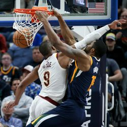 Utah Jazz forward Derrick Favors (15) is fouled by Cleveland Cavaliers guard Dwyane Wade (9) on a dunk, drawing the and-one, at Vivint Arena in Salt Lake City on Saturday, Dec. 30, 2017.