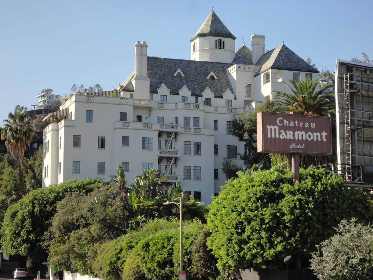 The exterior of the Chateau Marmont in West Hollywood, California. The facade is white with a grey roof and multiple towers.