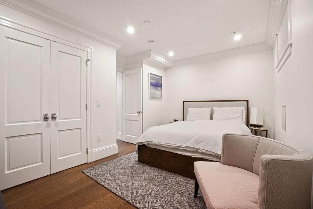 A bedroom with closed double closet doors and a large bed.