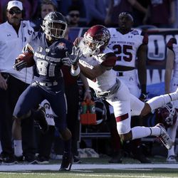 Utah State wide receiver Savon Scarver (81) breaks a tackle by New Mexico State defensive lineman Stody Bradley in the first half of the Arizona Bowl NCAA college football game Friday, Dec. 29, 2017, in Tucson, Ariz. (AP Photo/Rick Scuteri)